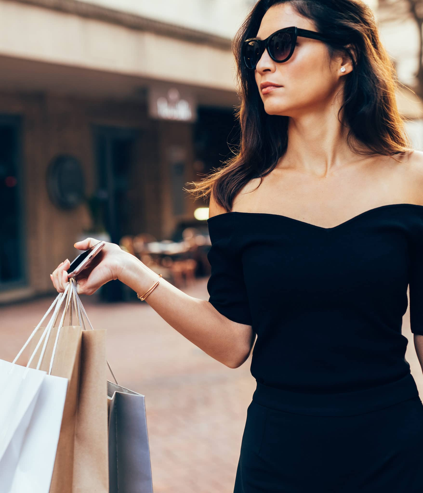 Stylish asia woman walking on the street with shopping bags. Beautiful female model outdoors in road after shopping.